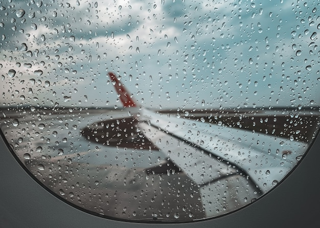 Rain drop at airplane window before take off when monsoon season.