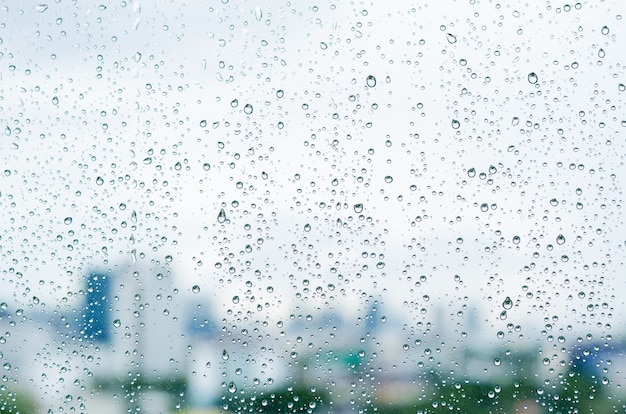 Rain drop on glass window at day time in monsoon season with blurred city buildings background.