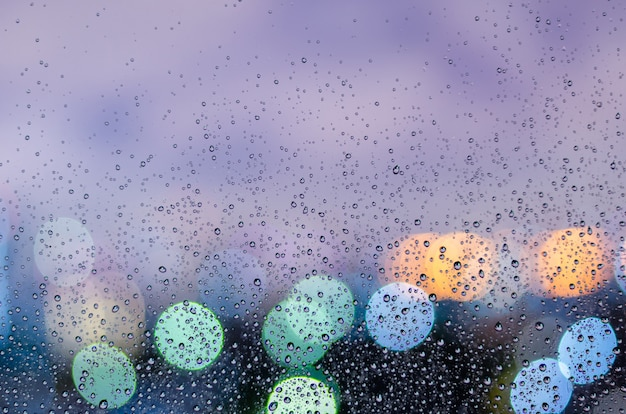 Rain drop on glass window in monsoon season with colorful bokeh light from city buildings background.