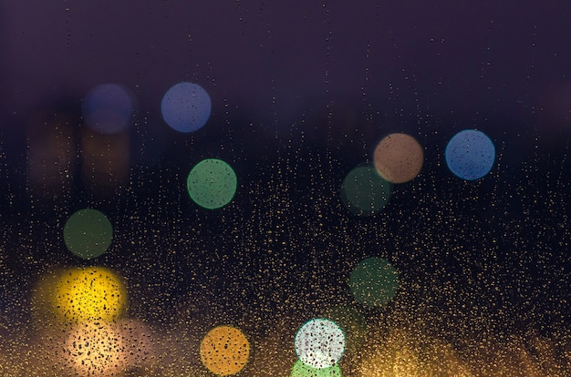 Rain drop on glass window in monsoon season with colorful bokeh lights for abstract and background