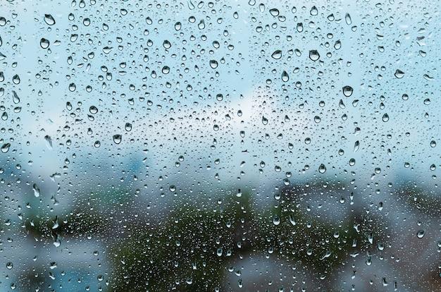 흐린 배경으로 몬순 시즌에 낮 시간에 유리창에 빗방울이 떨어집니다.