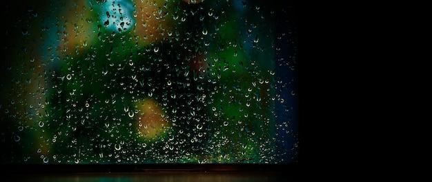 Капля дождя на окне ночью. кондоминиум или окно гостиной квартиры в дождливую ночь сезона в бангкоке, таиланд. за окном размыто размытое боке дождя городских огней и натурального дерева и неба.