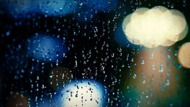 Rain drop on window at night. condominium or apartment living room window on rainy season night in bangkok thailand. outside window is blurred bokeh of raining city light and natural tree and sky.