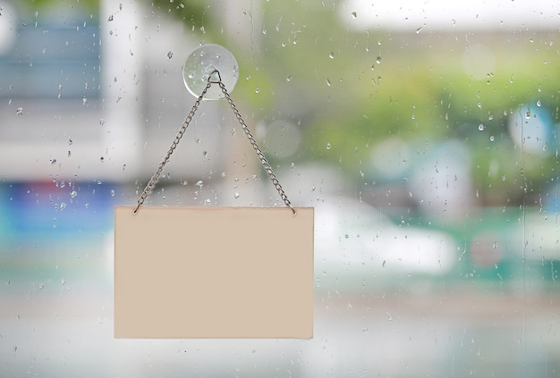 Rain drop with empty sign board hanging on glass door with copy space.