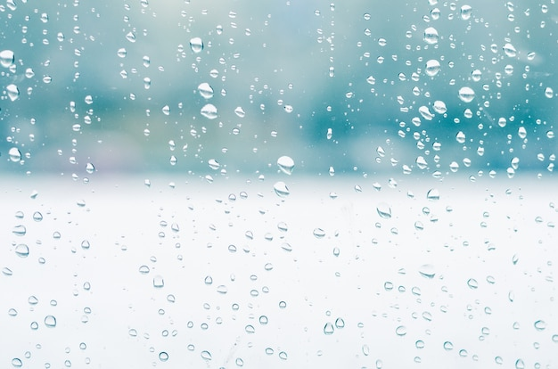 雨滴と窓ガラスの背景に凍った水、青い調子