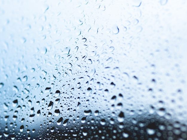 Rain drops on glass background. silhouettes of water drops on blue transparent surface.
