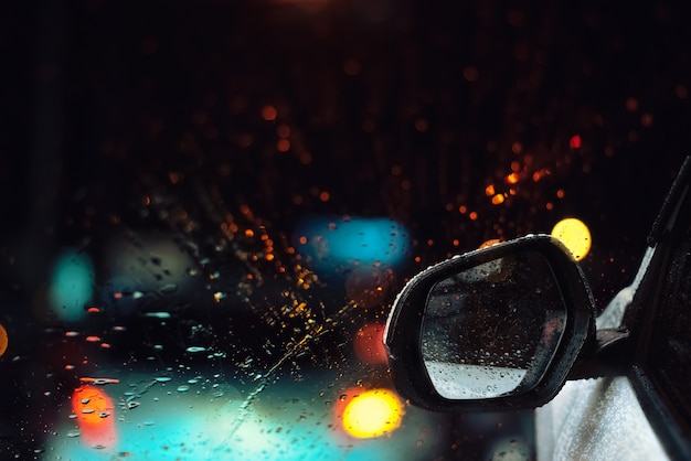 Rain drops on glass of car window with street bokeh at night in rainy season background