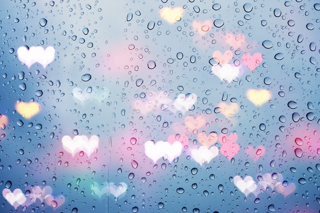 Rain drops on glass with abstract heart lights