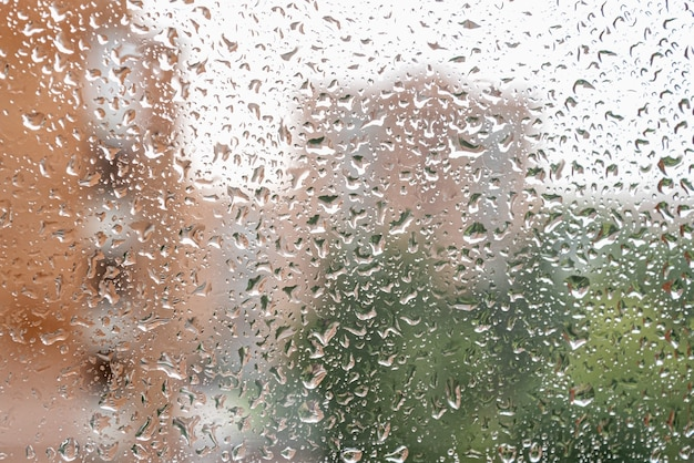 Капли дождя стекают на оконное стекло в дождливый день
