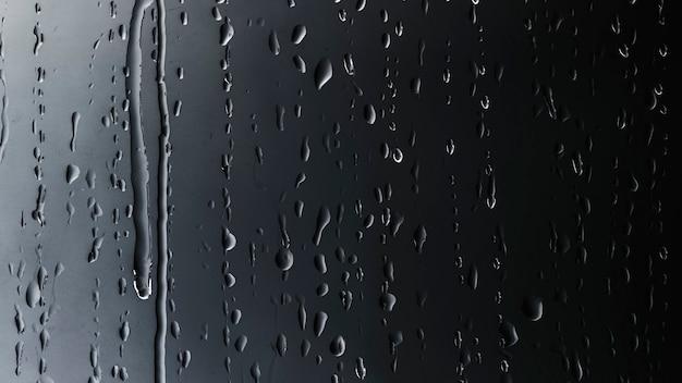 ガラスの黒い背景に雨が降る