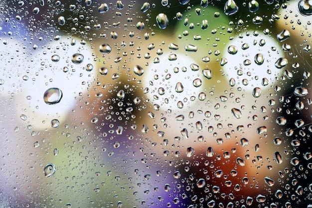 Капли дождя на стекле с красивым фоном
