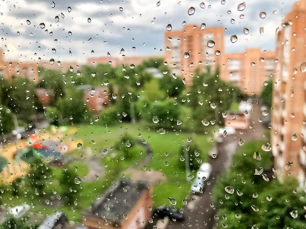 Капли дождя на оконном стекле в дождливый день летом