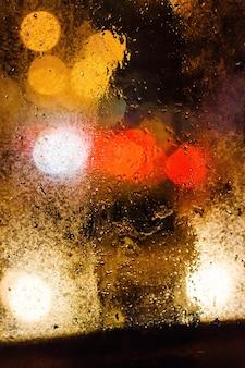 ボケ味で背景がぼやけているウィンドウに雨が降る