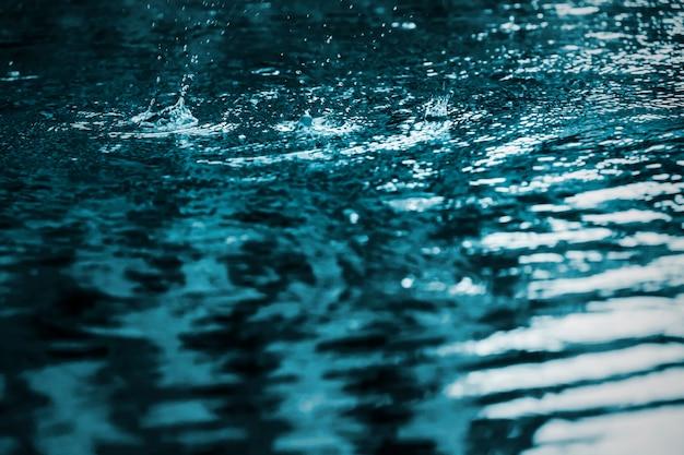 Rain drops splash in swimming pool