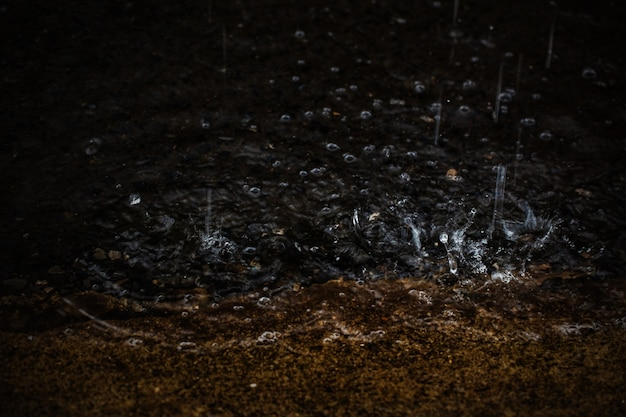 강한 비가 내리는 동안 튀는 비가 밤에 떨어집니다. 선택적 초점과 얕은 피사계 심도입니다.