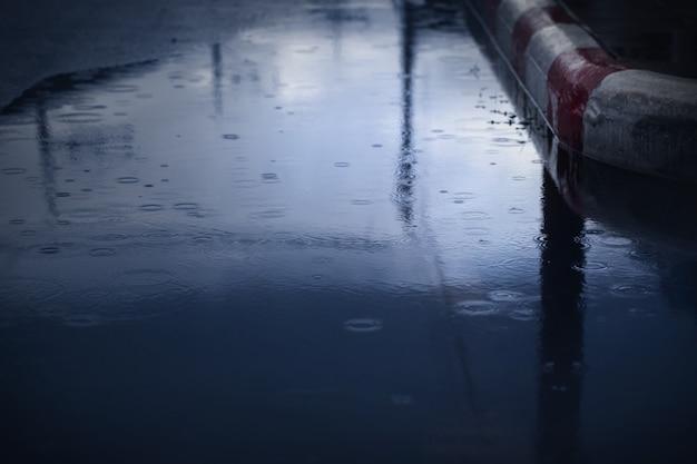 강한 비가 밤에 떨어지는 동안 튀는 방울, 선택적 초점. 장마 배경입니다.