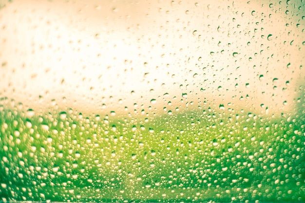 Rain drops on window glasses surface with sunlight background