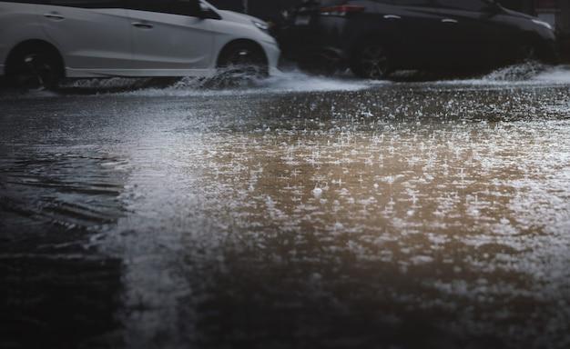 Падение дождя и наводнение в городе с размытыми автомобилями в качестве фона, выборочный фокус.