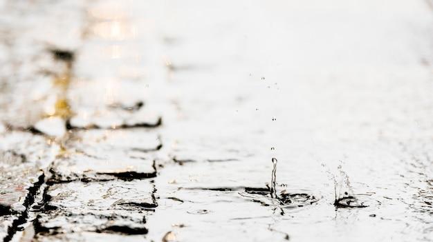 비가 도로에 내립니다. 밝아진 및 웅덩이 근접 촬영입니다. 비 개념입니다.