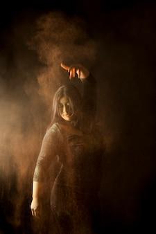 Дождь цветной пыли на индийскую женщину, танцующую на фестиваль холи