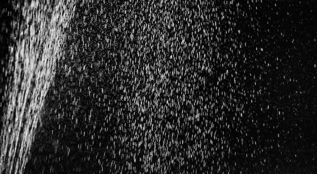黒に雨が降る。画面のブレンドモードと写真のレタッチのために、黒い背景に水のしぶきを抽象化します。