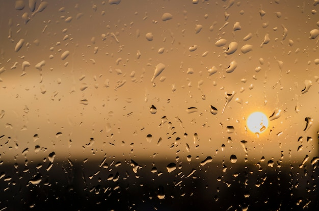 Rain outside window on background of sunset. rain drops on glass during rain. sunset outside window during raining. bright texture of water drops