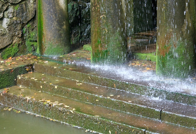 Rain and porch with pillars and steps (waterfall composition in old city park)