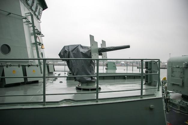 Rain-sheathed gun on a warship. steel front protection. rainy gloomy weather.