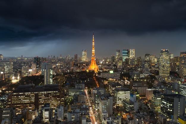 Шторм дождя над городом токио, япония в ноче с пасмурно над башней токио в японии.