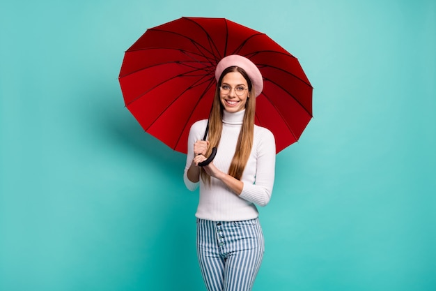 Дождь меня не остановит. фотография симпатичной путешественницы, держащей большой красный зонт, прогулка по улице за границей, хорошее настроение, одежда, характеристики, розовый берет, белая водолазка, полосатые джинсы, изолированные, бирюзовый цвет фона