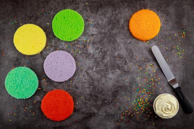 バースデーケーキを作るためのレインボーケーキ、フロスティング、ヘラ。
