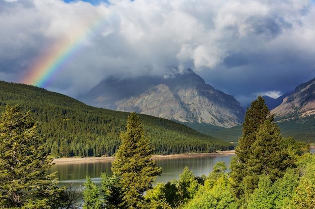 山の上の虹。美しい自然の風景。絵のように美しい自然。 Premium写真