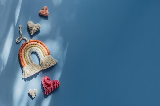青い背景に虹とハート。赤ちゃんと子供部屋のためのかわいい装飾とアクセサリー。フラットレイ、上面図