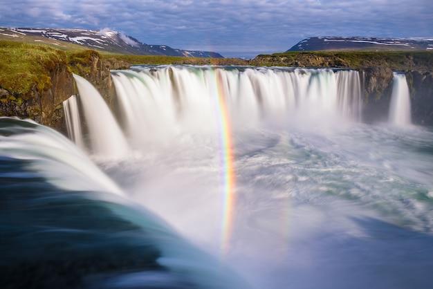 Радуга у водопада годафосс. природная достопримечательность исландии. удивительный летний пейзаж с каскадом воды и видами на зеленые холмы. солнечная погода