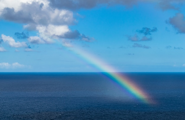 Rainbow in the atlantic ocean, with blue sky and with clouds