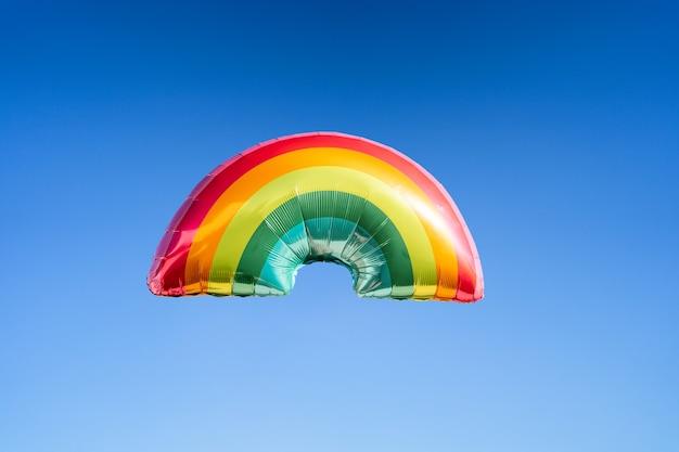 Радужный шар на фоне неба. понятие о лгбти. копировать пространство.