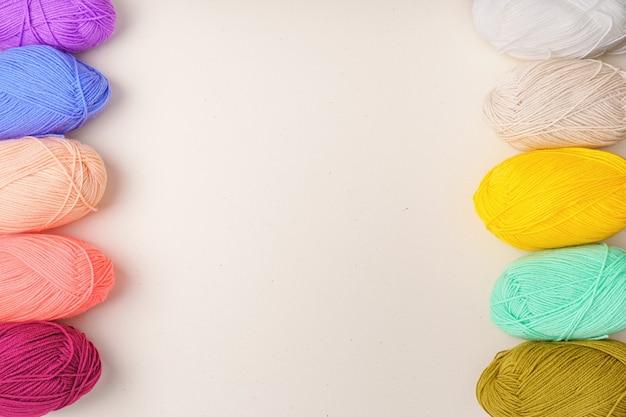 Rainbow balls of yarn is beige, yellow, burgundy, light pink, green, blue and white.