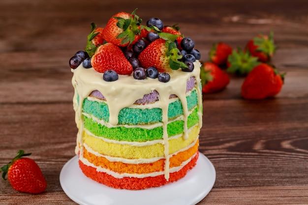 新鮮なベリーで飾られたレインボーバースデーケーキ。