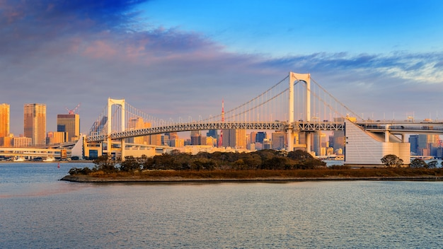 Rainbow bridge and tokyo cityscape at sunrise, japan.