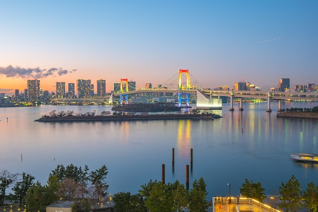Rainbow bridge with view of tokyo bay and city skyline in tokyo city, japan.