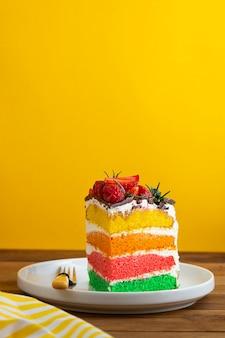 黄色の背景に新鮮なベリーとレインボーケーキ