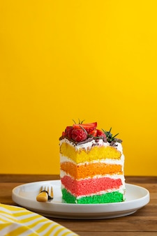 Rainbow cake with fresh berries on yellow background