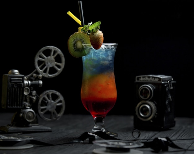 Rainbow coctail with kiwi and strawberries on the top
