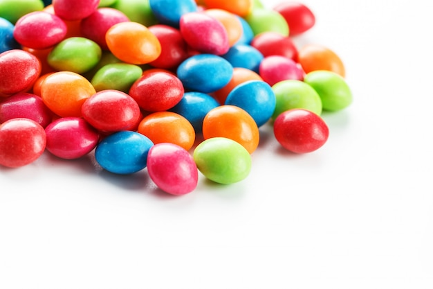 Rainbow-colored candies on white background