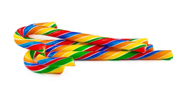Rainbow colored candy cane on white background