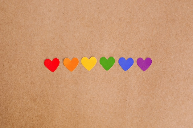 Rainbow colored hearts on kraft paper background. lgbt concept.