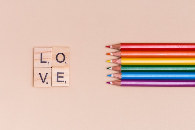 Rainbow colorful pencils and love letters on beige background