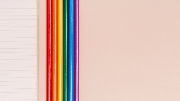Rainbow colorful pencils and notebook on beige background