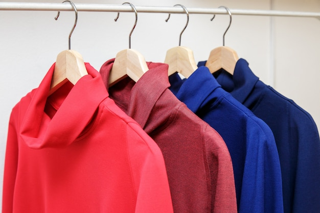 Rainbow colors. choice of casual clothes on wooden hangers in a store