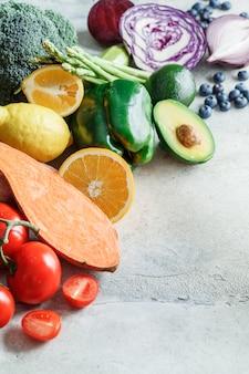 虹色の野菜と果実の背景。デトックス、ビーガンフード、ジュースやサラダの材料。